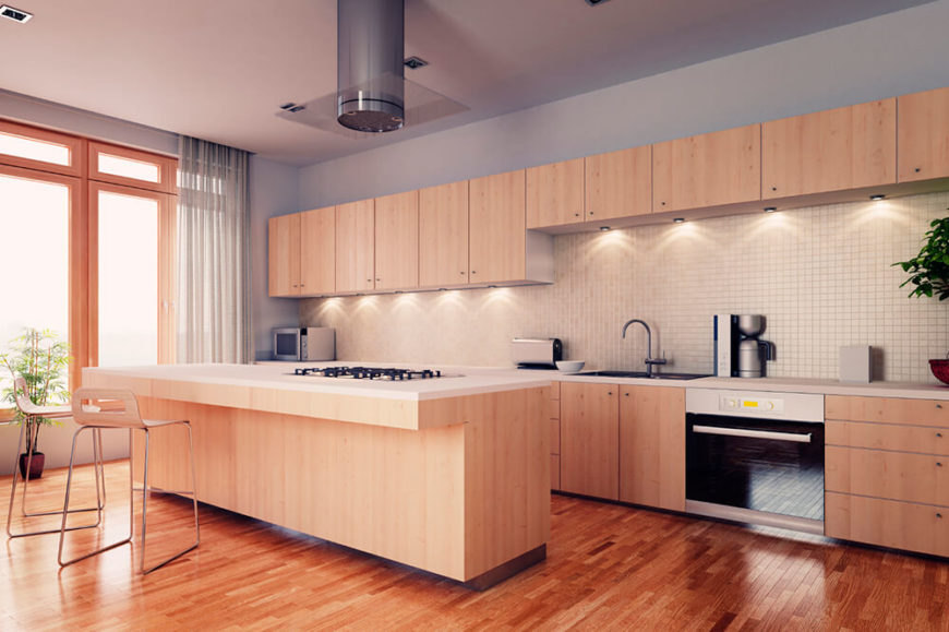 A light wood kitchen that merges modern design with a more traditional color scheme of light wood and gray walls. The expansive backsplash is entirely tiled in 1 inch white tiles.