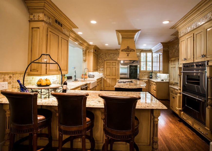 A beautiful kitchen with an expansive backsplash that runs floor to ceiling in some sections of the kitchen. The space also includes a massive island with a vent hood, an L-shaped eat-in breakfast bar, and dual ovens.