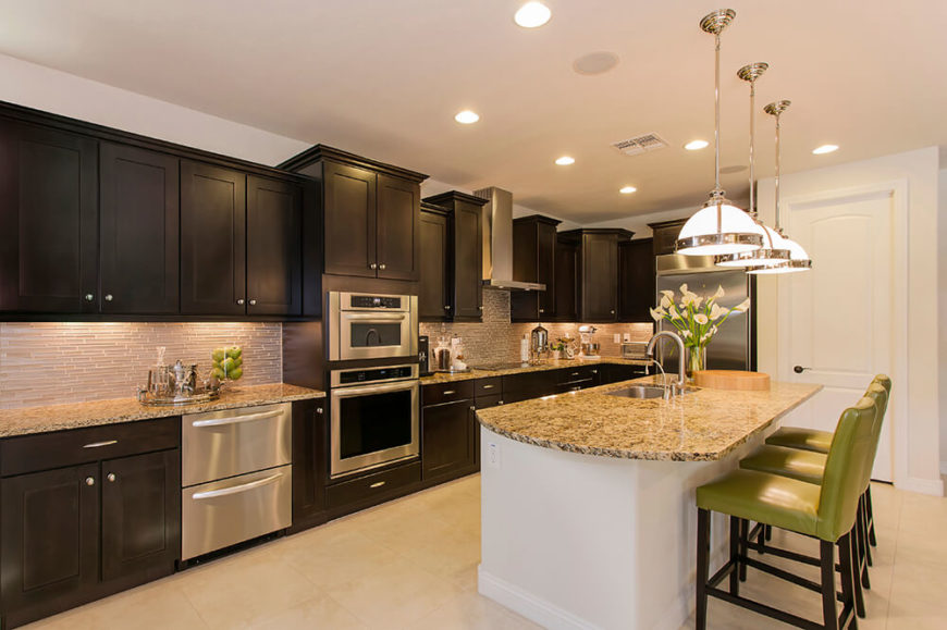 A contemporary kitchen with rich dark wood shaker cabinets, a white island, beige mosaic tile backsplash, and a few splashes of lime green as an accent color.