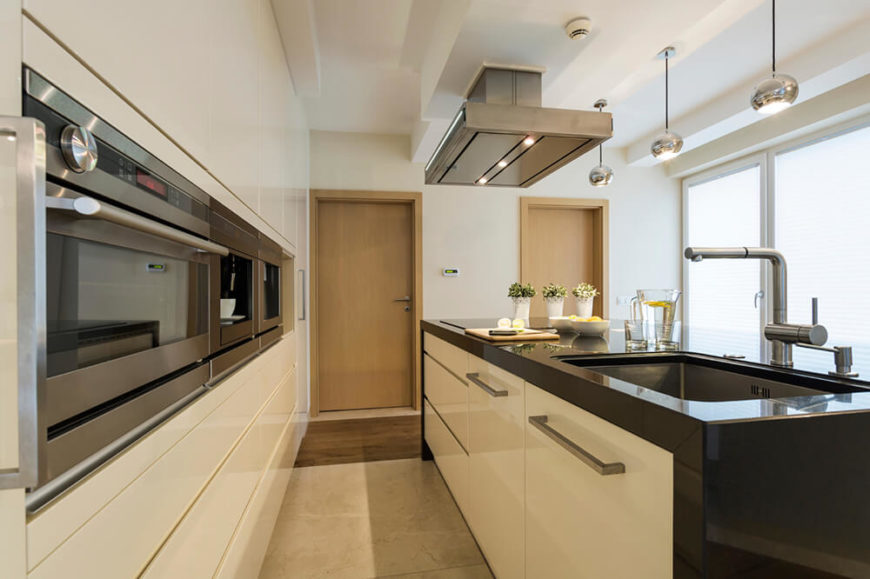 Another modern kitchen with a massive single-basin sink, sleek wall cabinets, and raised appliances in stainless steel. Industrial style faucets, vent hood, and pendant lighting add a bit of flair to the modern design.