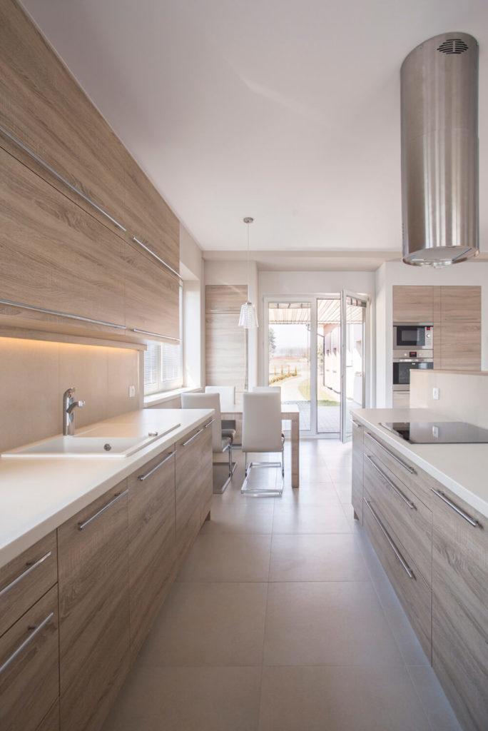 The ashen tone of this kitchen's cabinetry, when combined with the white countertops, backsplash, and tile, creates a light and bright kitchen and makes the space of a galley kitchen feel much more open.