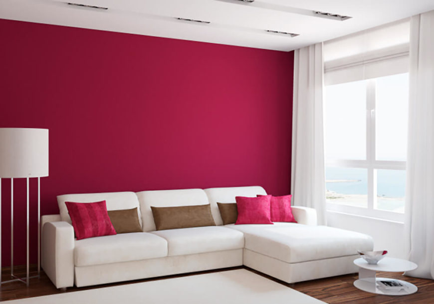 This living room is simple, yet vibrant. The bright pink accent pillows contrast the white couch and area rug, while the hot pink wall behind the couch gives the room a strong sense of character. Here, the lack of wall decoration is a statement in itself.
