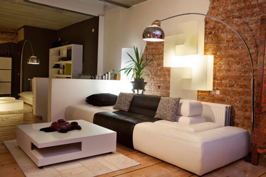 A unique space with modern furniture and low, calm lighting. This living room wall features accent bricks and an abstract lamp mounted on the wall.
