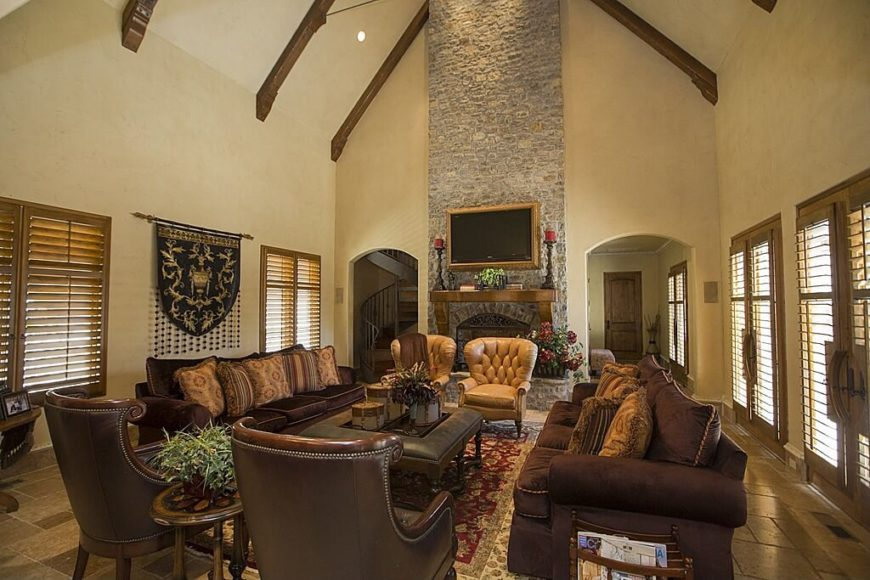An extremely high ceiling makes this living room feel quite spacious and gives the room a strong sense of depth. Rich leather furnishings are featured, while on the wall hangs a family crest banner, and adjacent to that is a grand stone fireplace.