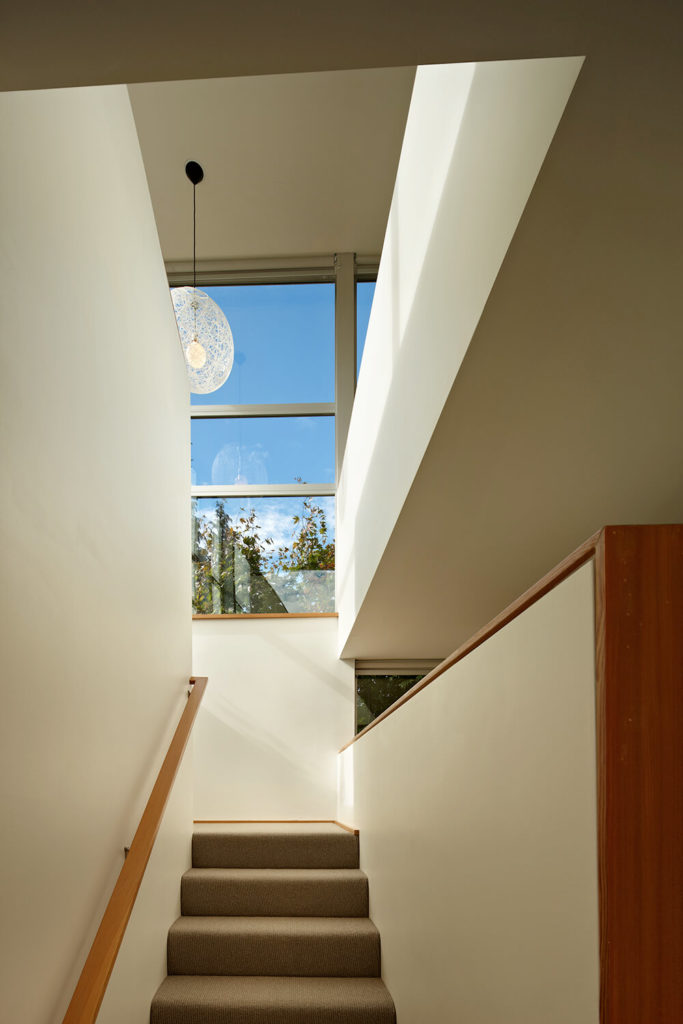 Continuing up the stairs, we can see the large seamless windows that start to reveal the view of the lake and of downtown Seattle. Visible from this angle is the lovely string-like globe light centered between the two stairwells.