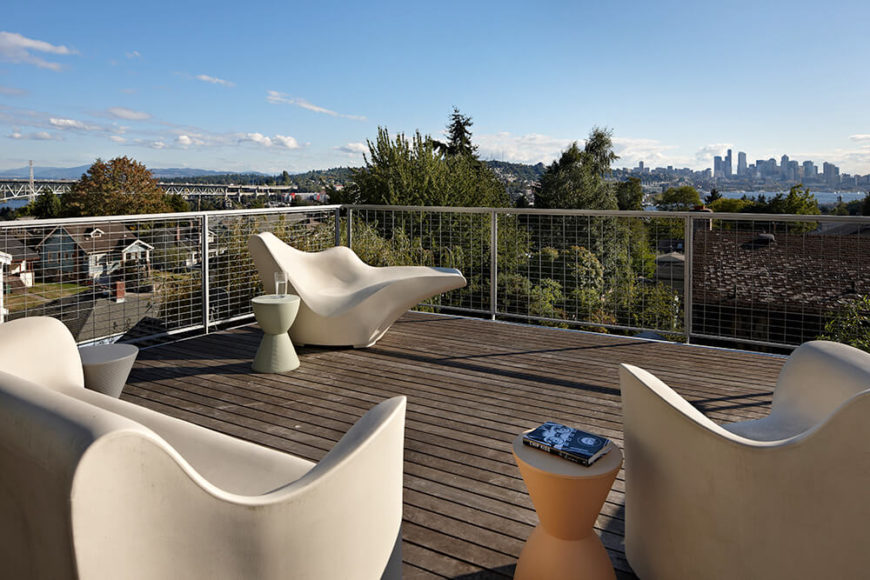 The rooftop patio has a high balustrade, dark decking, and a variety of nebulous modern seating in white. From the roof, we can see a large bridge, the lake, and the city skyline.