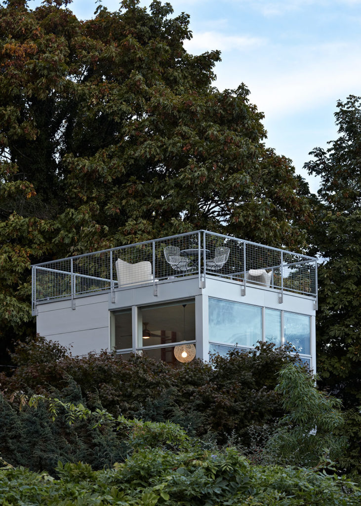 From this angle, we can see the top of the third floor and the rooftop patio. The lot is heavily forested, and the treetops obscure much of the tower, preserving the owner's privacy in the glass-wrapped home.