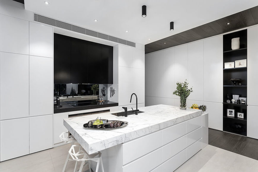 The kitchen itself is defined by a large white island with thick white marble slab countertop and built-in sink. The black hued range stands flanked by sleek white cabinetry, as does a slim display shelf at right.
