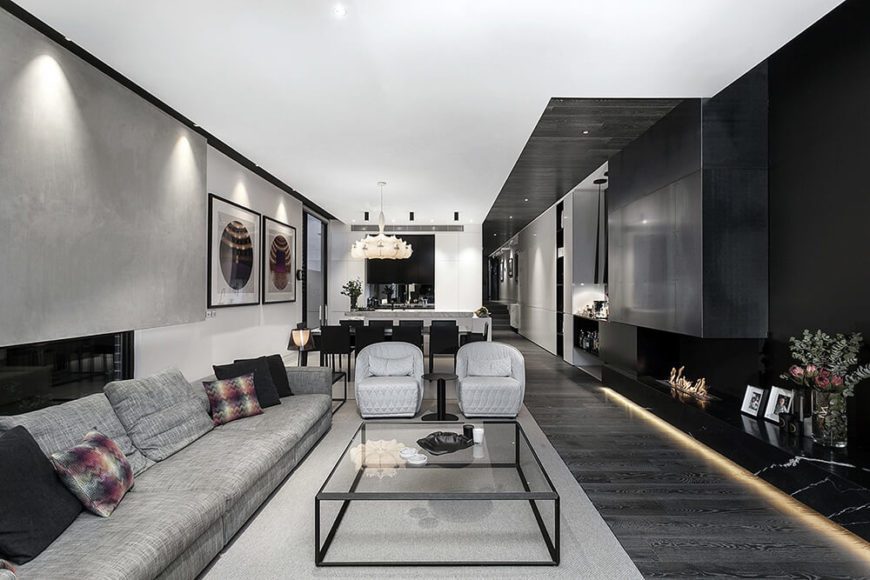 With the home being a lengthy, relatively slender open volume, we can see the black of the living room give way to a light grey tone on the walls as the open space transitions into the kitchen. Beyond that lies the main hallway.