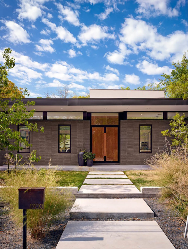 Across the large stone slab walkway we see the unassuming home, with slimmer windows on the front and a low, broad flat roof obscuring the brightly open space within.