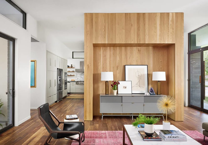 The living room is defined by a large natural wood feature wall, with a cove that hugs a midcentury modern dresser in grey. We can see sliding glass entryways for the backyard and side flanking this open space, with the kitchen and dining in the background.