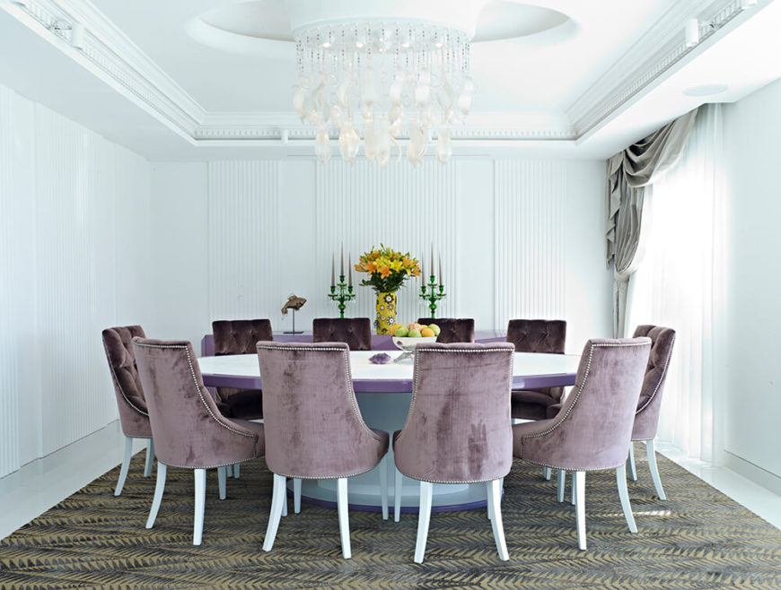 The dining room features subtle texturing on the walls and ceiling, with a unique chandelier hanging over the massive purple-rimmed table. A set of nailhead trim Parson chairs wraps the table over a floral print rug for high contrast.