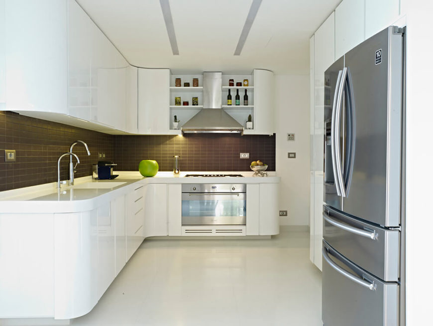 The kitchen is all sensuous curves and sleek surfaces, with white cabinetry and countertops over white tile flooring. Contrast and texture are provided by the subtle dark subway tile backsplash and stainless steel appliances.