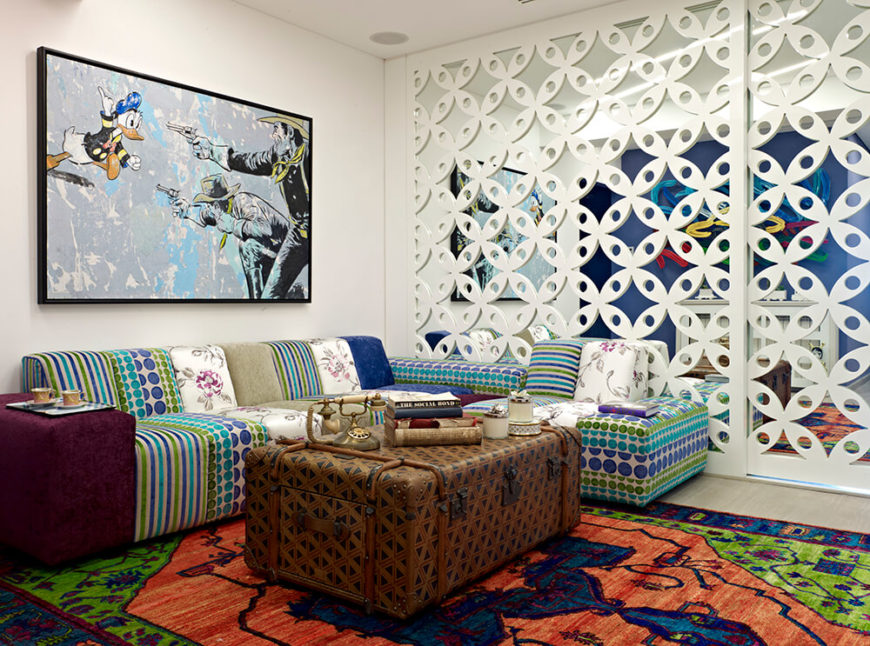 The multi-textured sectional reflects the rainbow explosion around it, wrapping a large trunk-style coffee table. A patterned dividing wall with a mirror backing adds a host of texture and expands the visual space.