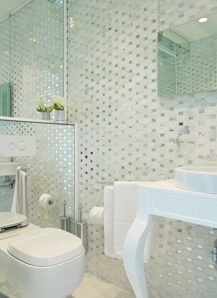 Here's one of the bathrooms in the home, a small space that employs mirrors to expand its visual size. A white vanity with vessel sink stands against a highly textured wall at right.