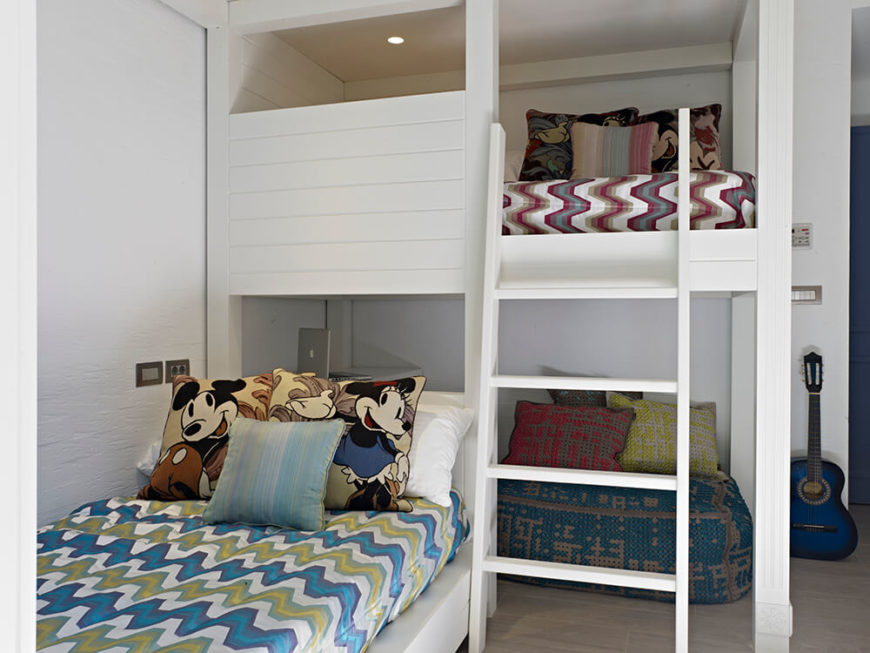 This second kids room features another loft bed design, hanging over a small home office space that's perfect for studying or relaxing. More detailed patterns cover the bedding here.