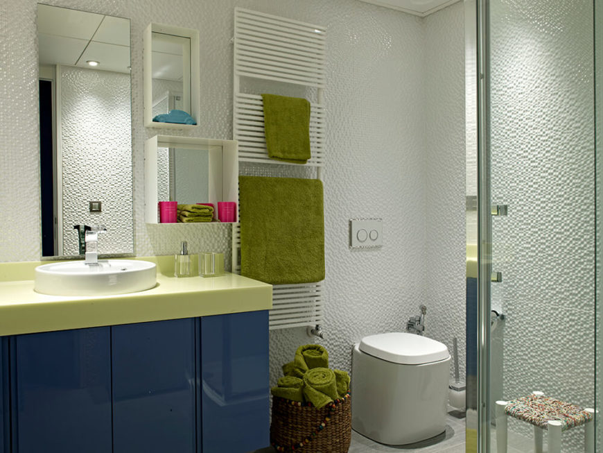 Here's a second bathroom, flaunting a completely different style than the first. A dark blue and yellow vanity stands below a series of mirrors that incorporate shelving, while a highly textured wall makes the white space more detailed.