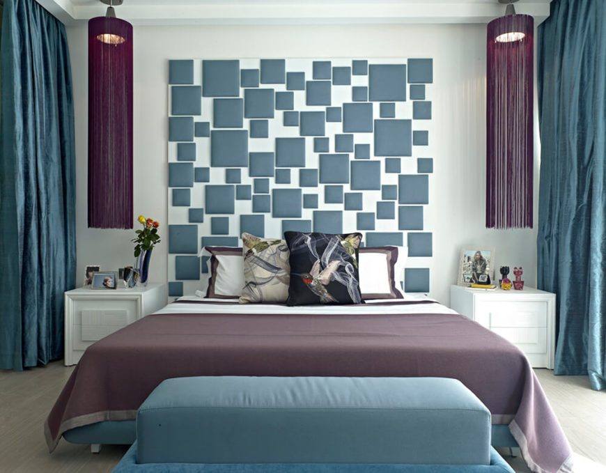 The primary bedroom features a bespoke color palette, making for a cohesive space. The standout feature is a unique full height headboard with colored squares on a white backdrop.