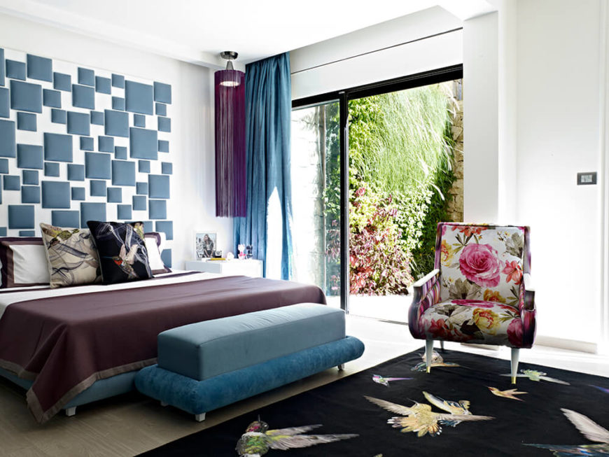 The primary bedroom features a sliding glass door for direct patio access. A large black area rug features a hummingbird design, matching a decorative pillow on the bed itself.
