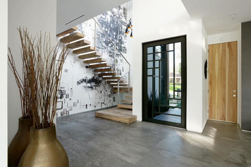At the front entrance of this home, you step into an open space with a unique staircase to the side. The floor is textured and compliments the patterns on the wall behind the stairs. Immediately you are greeted with this modern design.