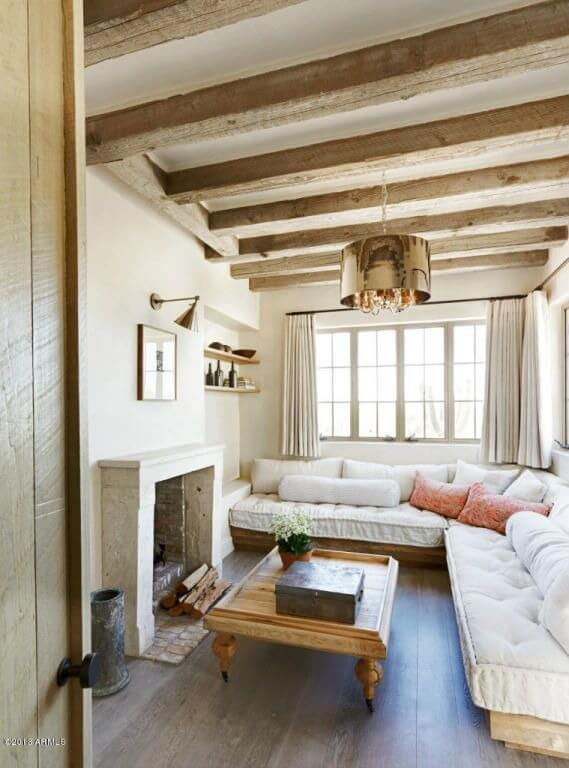 This cozy living room features a mixture of modern tones and rustic charm, with exposed natural wood beams above and rich hardwood flooring below. A white cushioned sectional wraps two of the walls, hugging an arrow foot coffee table facing the fireplace.