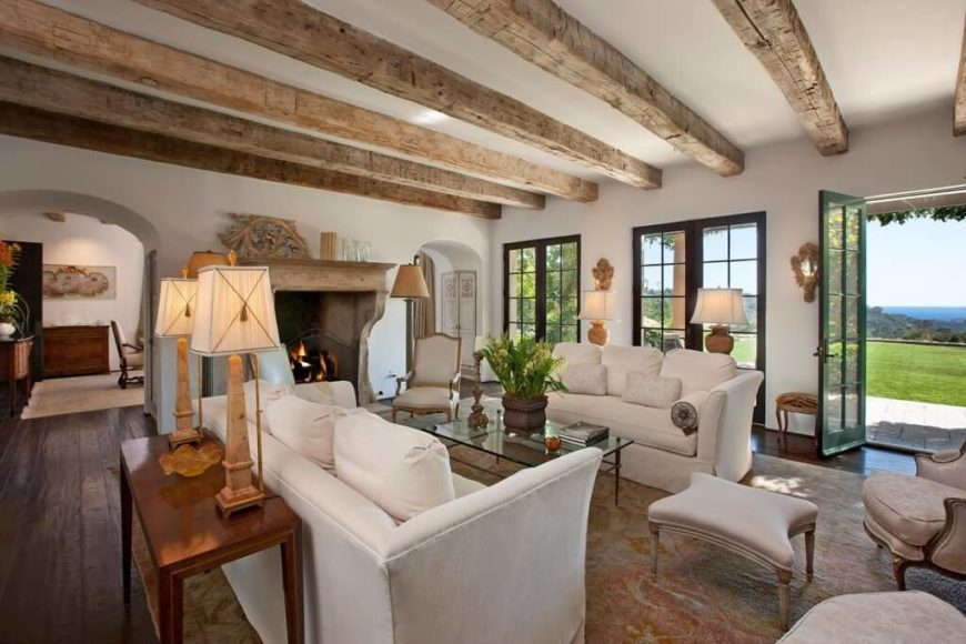 In an immense living room mixing rustic and contemporary styles, we see natural wood ceiling beams hanging above a pair of white sofas and a glass topped coffee table. A set of traditionally styled armchairs also populate the large central area rug.