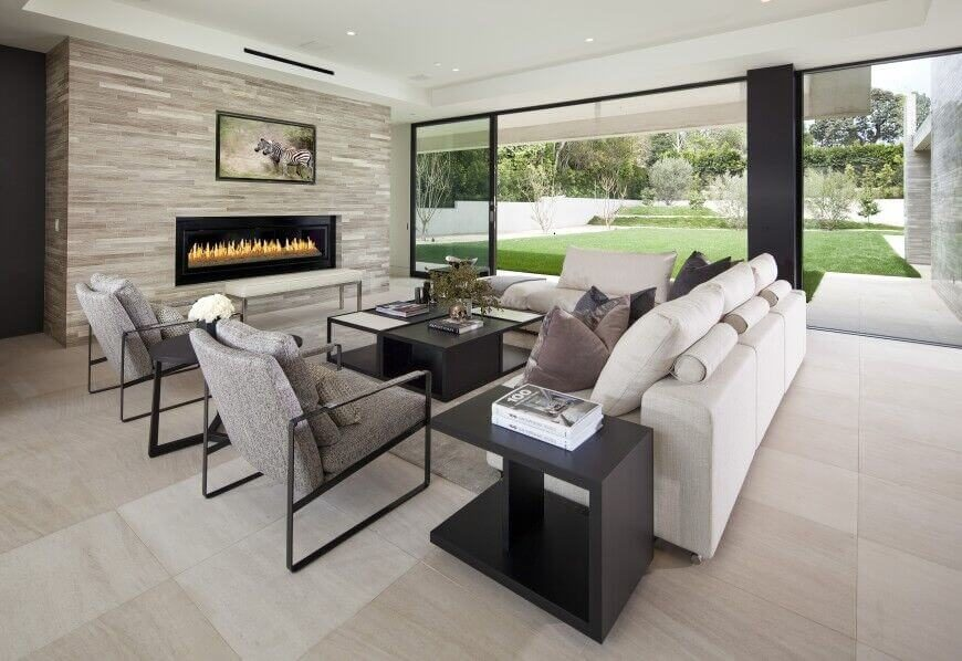Here's another sleekly modern living room wrapped in full height glazing for a truly open, expansive visual presence. The room centers on a set of contemporary furniture including an L-shaped white sectional, facing a large gas fireplace in grey brick.