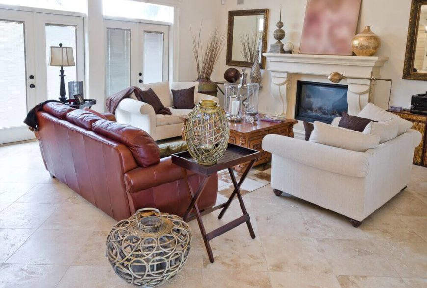In a cozy living room centered on a large fireplace, we see beige marble flooring supporting both a brown leather sofa and pair of white roll arm love seats. At the center is an ornate carved wood coffee table with built-in storage.