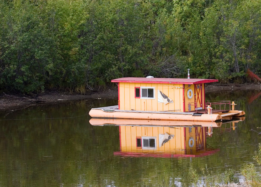 "A more rustic ""shanty"" houseboat. Shanty boats are small homes floating on rafts, which distinguishes them from houseboats. This shanty boat is brightly colored"