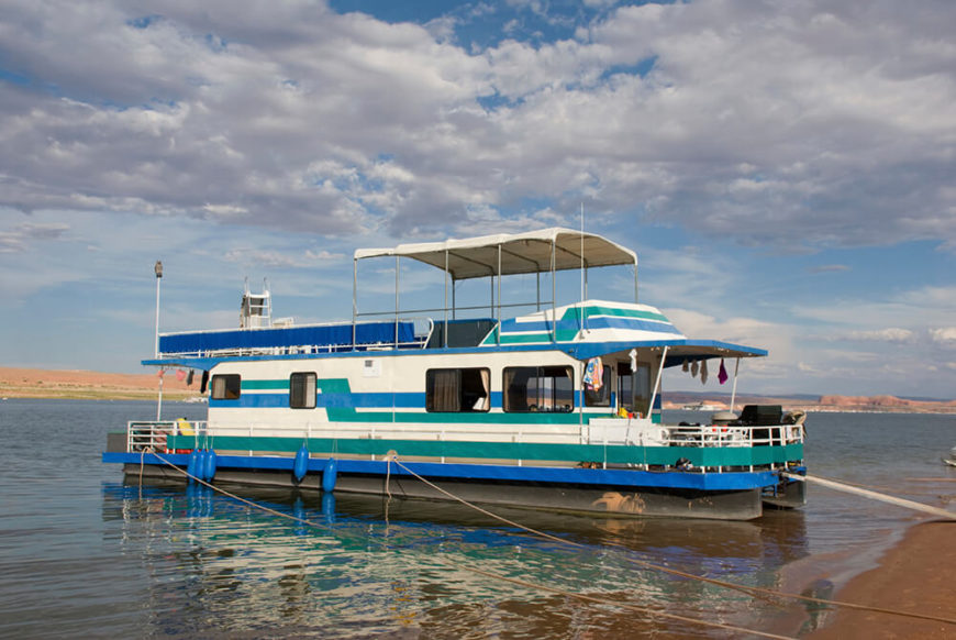 A large houseboat with two covered decks and a large enclosed living area. This boat is large enough to be used for leisure cruises, and is currently moored off of a beach.