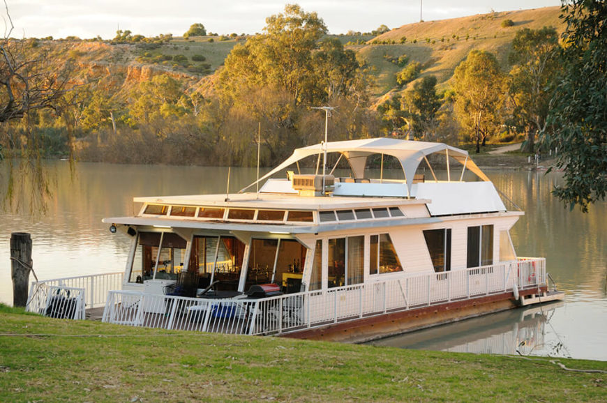 A large luxurious house boat with a covered deck at the top and a large seating area on either side of the boat. The inside is dotted with windows so the owners can enjoy the view.