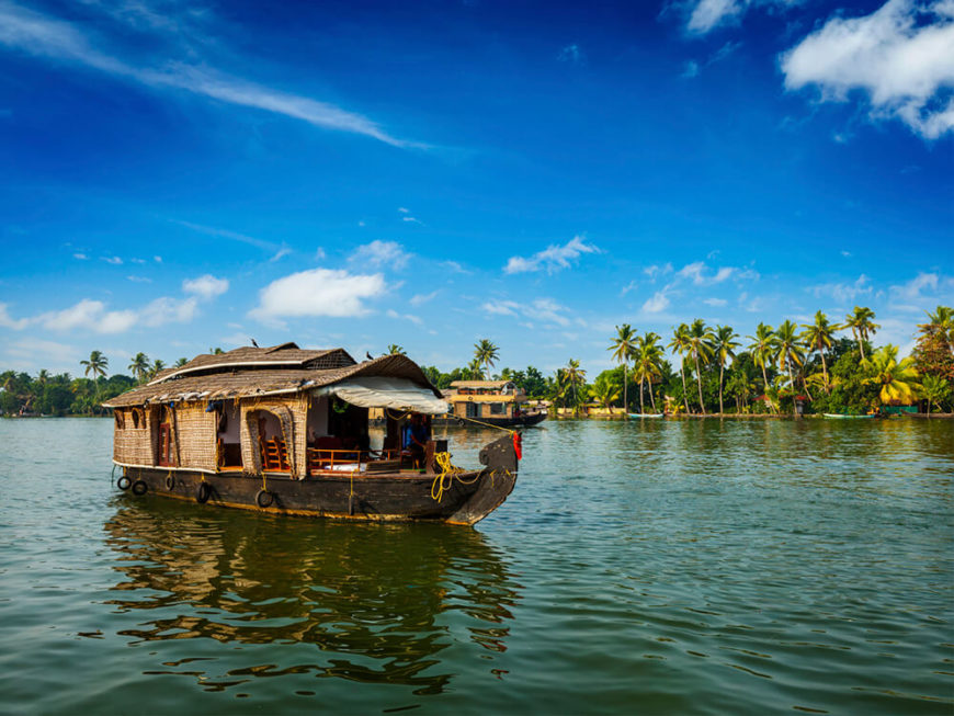 This houseboat in Kerala is moving slowly down a wide river, perfect for sight seeing.