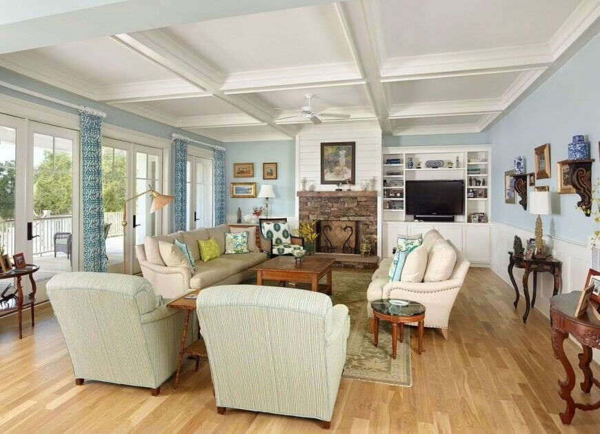 Antiques have a space in more contemporary homes as well; this lovely coastal contemporary living room features a few antique side tables and shelves in addition to the contemporary sofas and chairs.