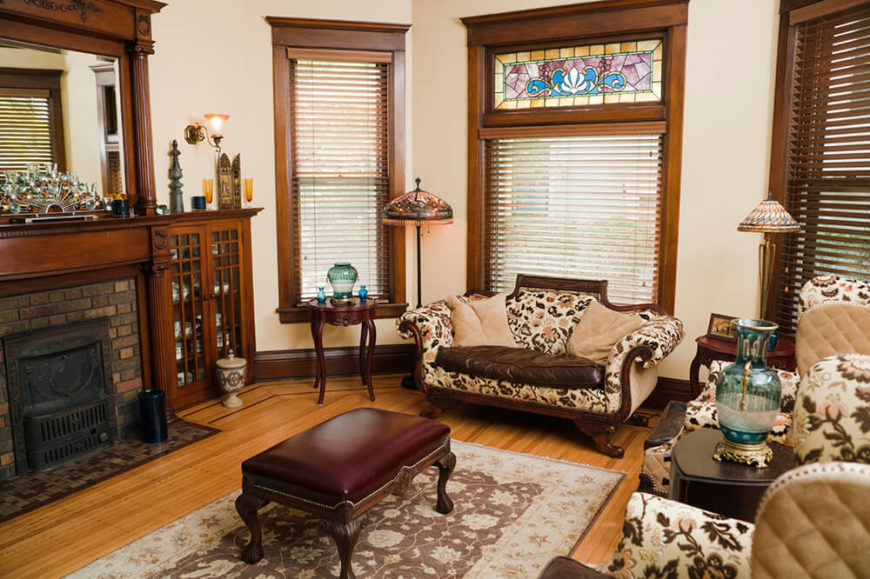 A lovely formal living room an an antique fireplace with a cast-iron cover, a built-in mirror mantle, and a wealth of beautiful original woodwork. Tiffany lamps and a stained glass transom round out the room with color.