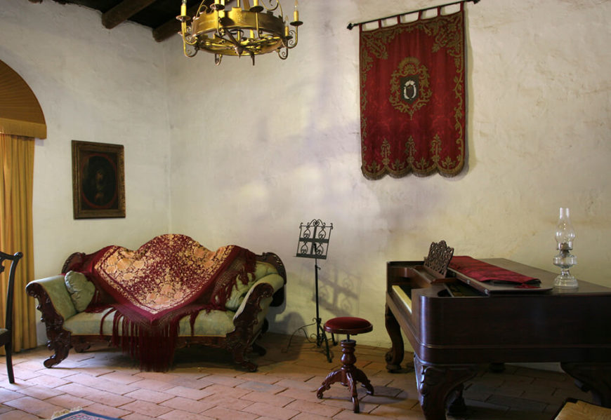 Period-style living room with piano and tapestry.