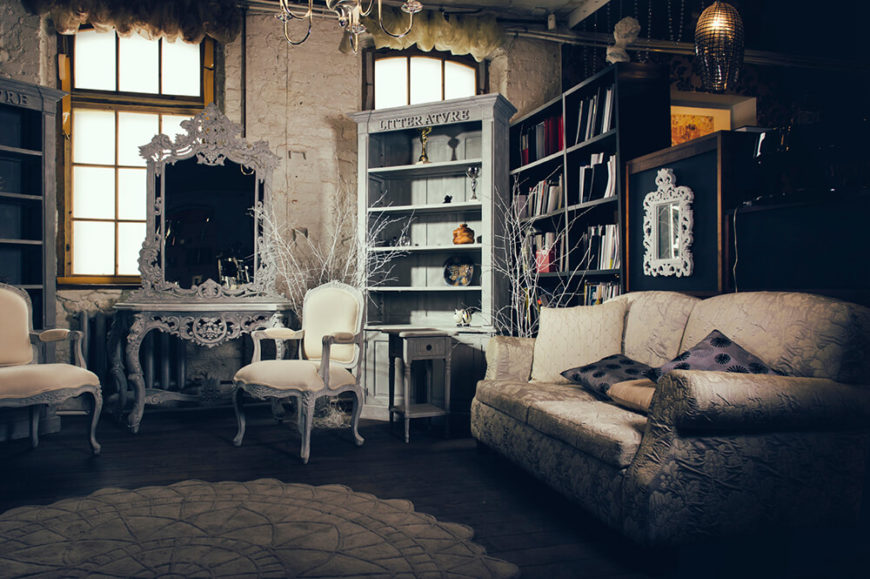 This living room has an interesting arrangement of antiques, including an old vanity, bookcases, armed dining chairs, and a cushy, floral patterned sofa. Note that a few of the antiques have been painted white to help brighten up the somewhat dark space.