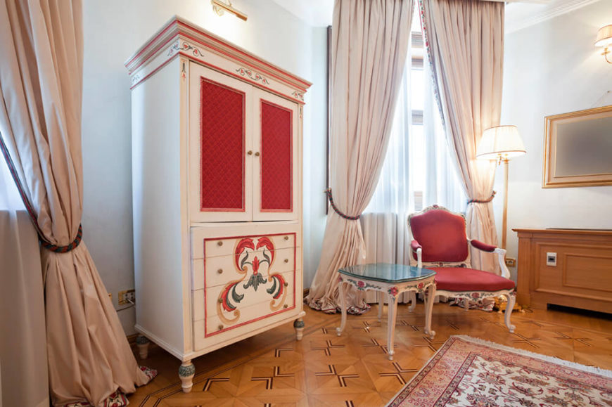 This beautiful living room has lovely parquet flooring, built-in features, and a wealth of windows that are covered with ballooned curtains. The antique furniture is in white with hand-painted details and panels.
