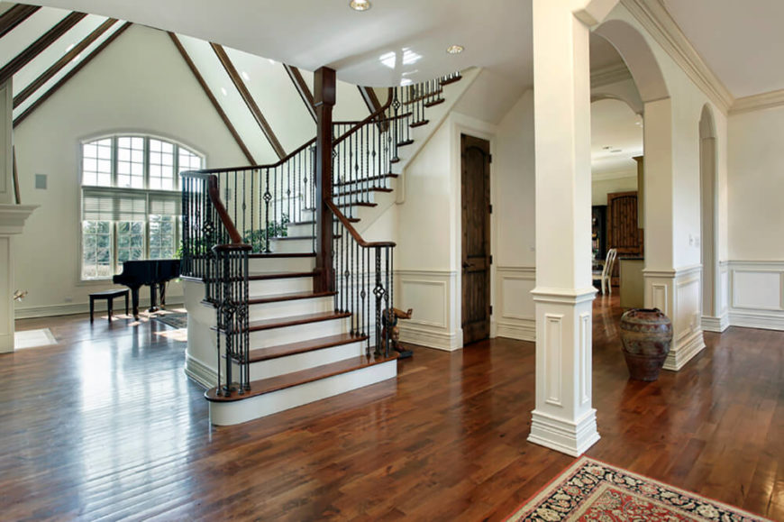 The wainscoting on these walls keeps them from being too flat in all the white of the house. The dark wood accents stand out nicely against the white and compliment both the floors and the black metal banisters surrounding the centerpiece of the room - the stairs.