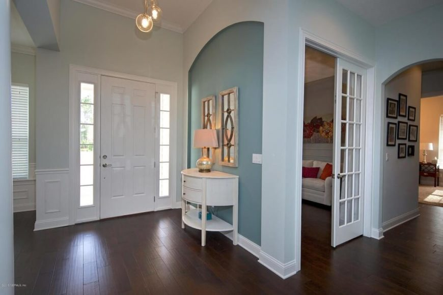 Depth is added to the pale teal walls by the darker inset piece of wall next to the front door. The dark wood floors are offset by the white trim and wainscoting in the room. Warm red and orange accents can be seen through the french door to the right. These colors make a great accent color for the teal walls.