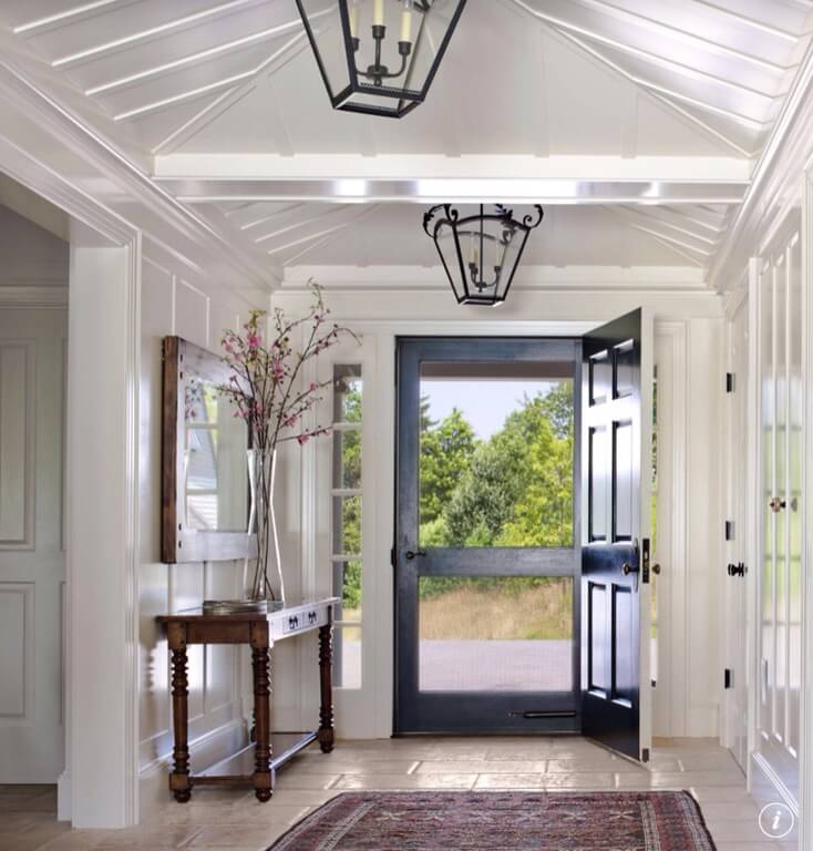 This gorgeous white wainscoting fills this foyer with so much extra light. The room is grounded by the dark wood of the door and the side table while the addition of flowers and a plush rug softens the room considerably. The peaked ceilings are highlighted by the black lanterns with whimsical curls or wrought iron.