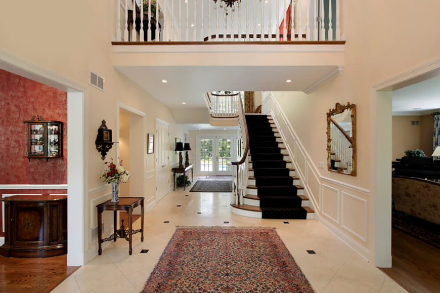 Finishing up this central corridor to the home in pale tones and white creates a simple backdrop to the rich colors seen in the rest of the rooms. The color from the other rooms is pulled into this foyer by the rugs and the runner on the stairs, offering hints of what the rest of the home holds.