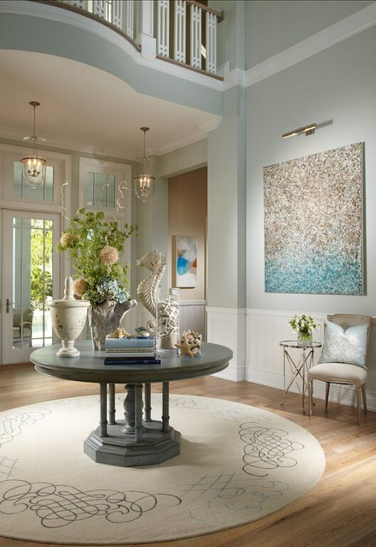 The use of pale colors in this room successfully creates the nautical theme of this design. The pale blue of the walls is carried throughout the room in subtle accents like the pillow, or in the flower arrangement on the center table. The white wainscoting highlights the beige and off white colors used to bring out the blues and peaches better.