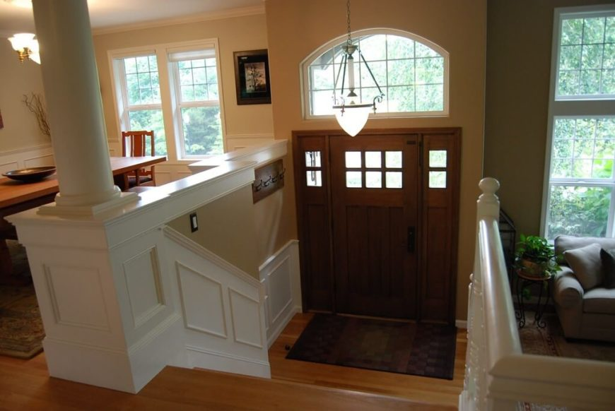 White wainscoting freshens up this narrow space. Despite being open, the tall wall to the side of the door blocks much of the light and makes the foyer dark. Including the wainscoting helps to reflect some of the light that reaches it so as to counter the dark wood of the door.