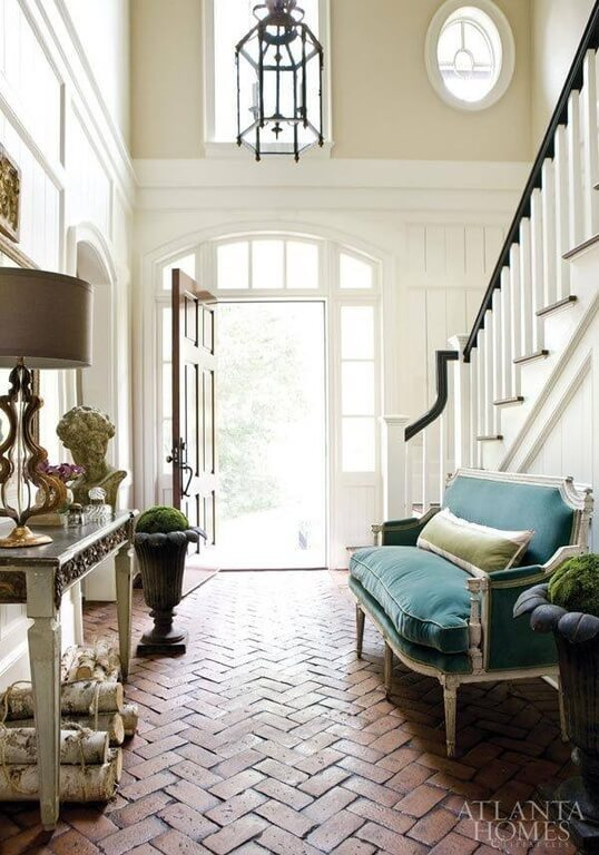 Patterned brick floors set this room apart and balance the brightness of the room with a dark, rough texture. Antique furniture contrasts the rustic aspects of the floor and dark planters used in the room to give it a charming, whimsical feeling.
