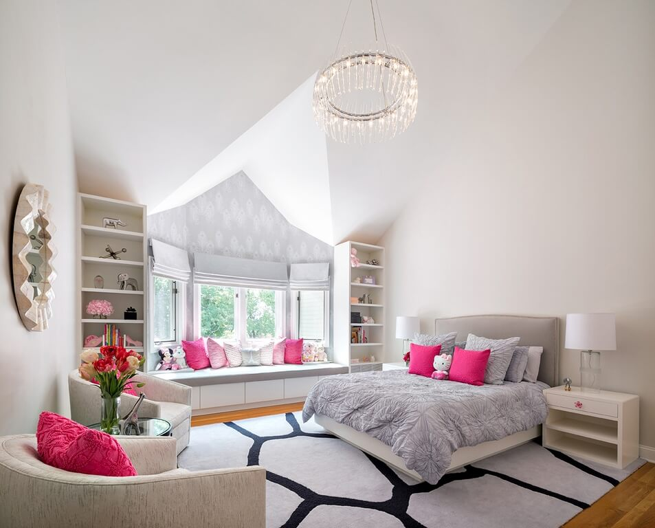 Large girl's bedroom with a large bed and a sun area with bench seating and multiple throw pillows. The rug looks classy while the seats look cozy.