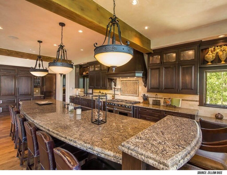 The leather chairs added to this room match the shade of the lower cabinets in the stately kitchen design. Light countertops match the colors of the tile backsplash and offsets the dark wood of the cabinetry. Large pendant lights add a soft glow to the room.