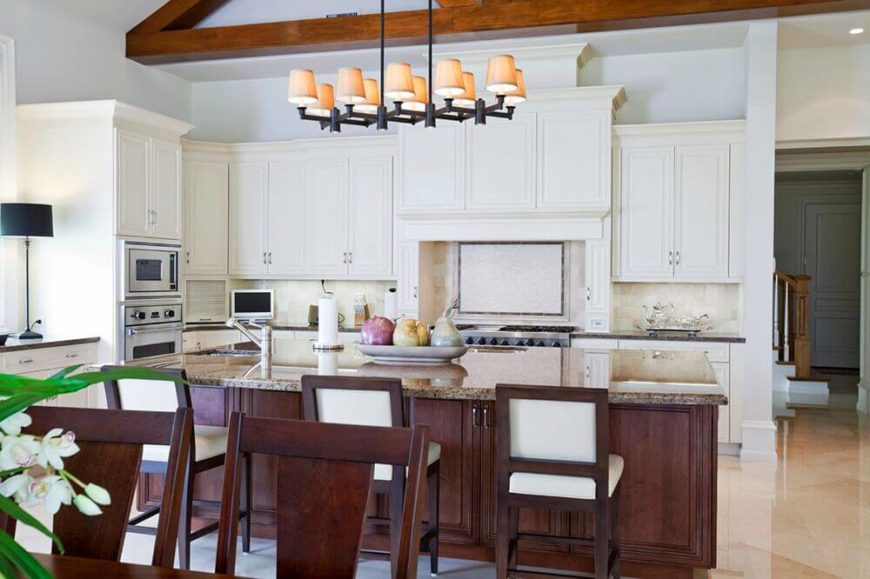 The chairs in this kitchen help to carry the contrasting color of the island further into the kitchen and break up the pale colors dominating the space.