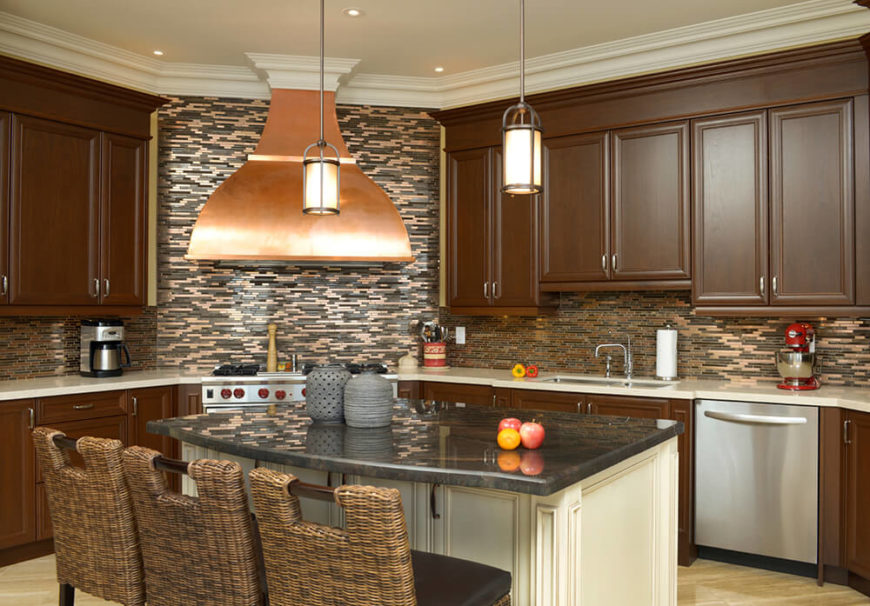 Browns, grays, and golds create this room which is centered around the showcase piece of the copper stove hood, which visually dominates the room. Metallic tiles in the walls carry the finish around the room and breaks up the flat chocolate brown of the cabinets. Wicker chair backs mimic the patterning in the backsplash.