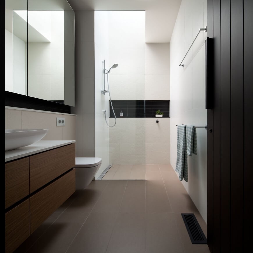 Primary bathroom features a wooden floating vanity topped with white marble and a vessel sink. It has a walk-in shower accented with a black subway tile backsplash.