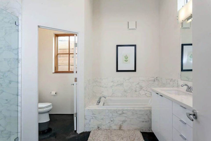 In the bathroom, we see more of the light marble tiling that informs the kitchen, wrapping around the vanity and bath area. This room also features a discrete commode and a glass-enclosed shower.